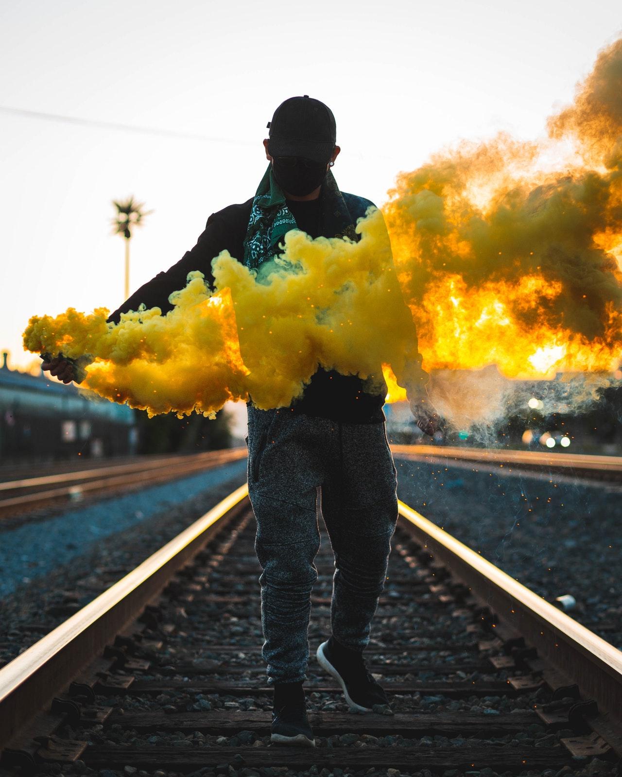 photo of man standing on train tracks holding a yellow smoke 2273392